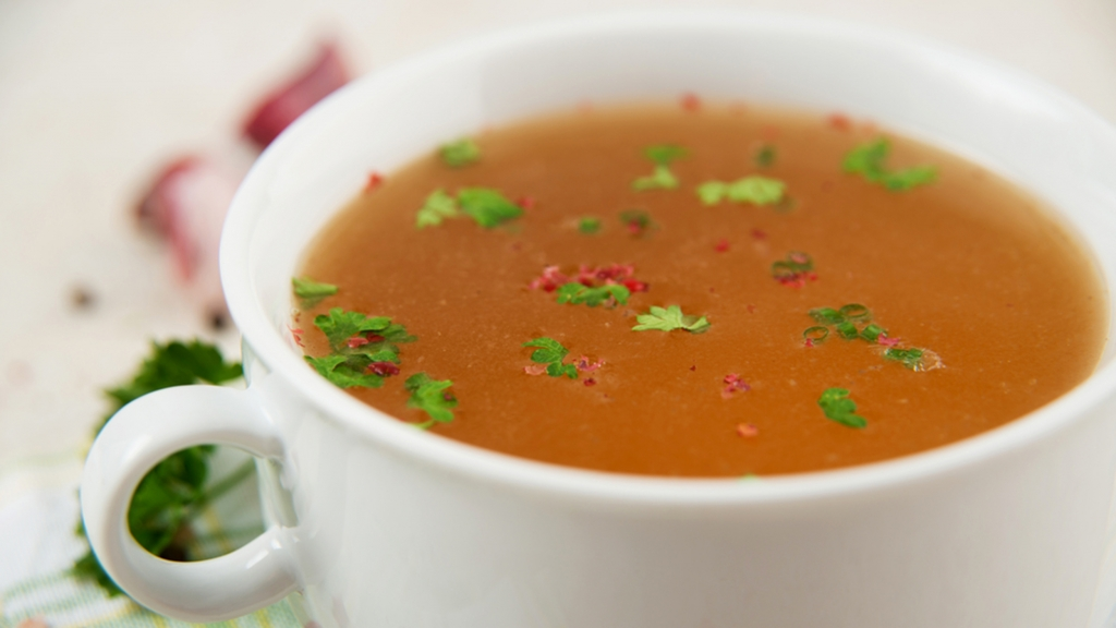 Bone Broth in Small Soup Bowl Served with Fresh Herbs, Garlic and Spices; Shutterstock ID 144087859; PO: TODAY.com